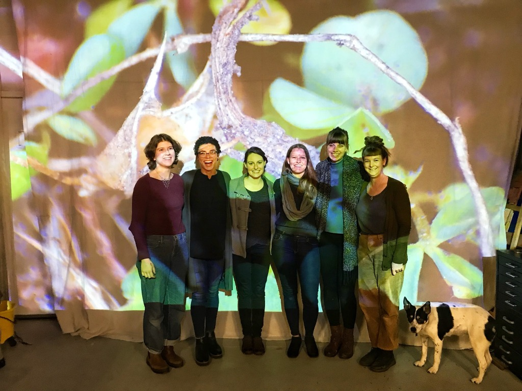 Image contains: 6 people, people smiling, in front of large projections of plants. Cute dog named banjo.